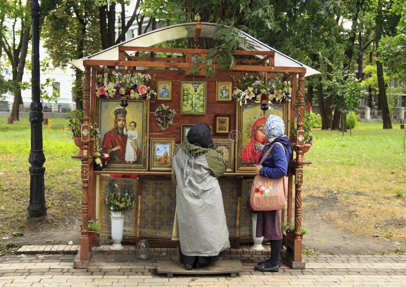 正统妇女在象前祈祷在公园 免版税库存照片