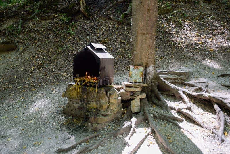 正统蜡烛在森林里在箱子的一棵树下 由路的祷告石头 图库摄影