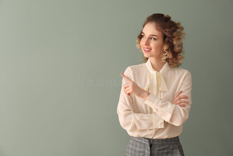 正装的美丽的年轻女人指向某事的在颜色背景 库存图片