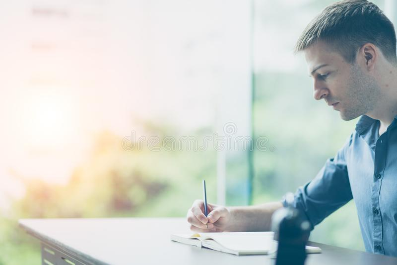 正认为的概念 坐书桌和写在有拷贝空间的笔记本的一个英俊的商人的画象 库存图片