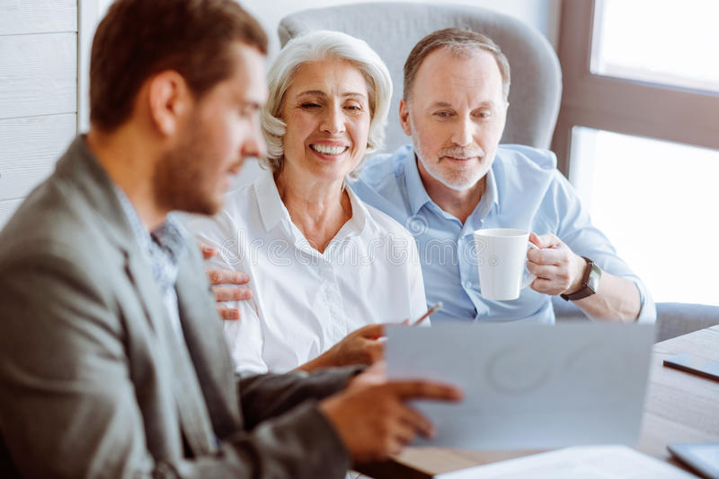 正面与保险代理公司的年迈的夫妇会议 库存图片