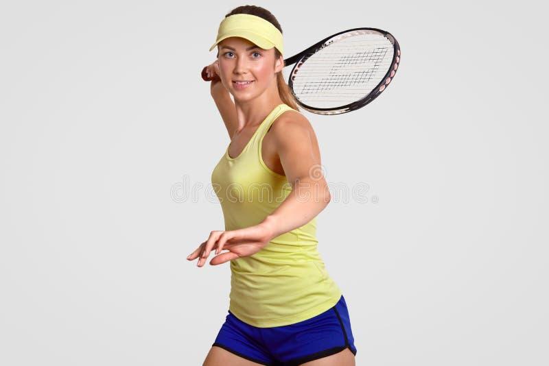 正面健康活跃运动的妇女在比赛前做准备,穿戴在偶然成套装备,准备好击中与raquet,姿势的球反对 库存图片