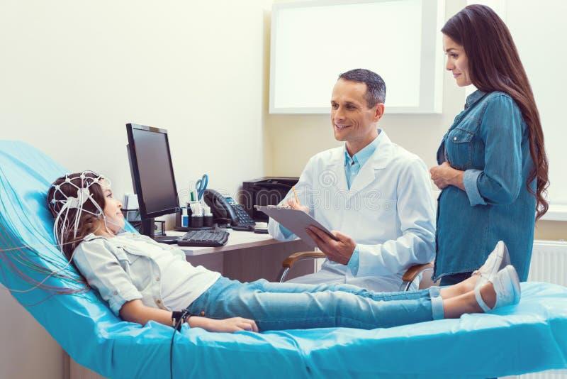 正面医生和母亲谈话与接受脑波记录仪的女孩 库存照片
