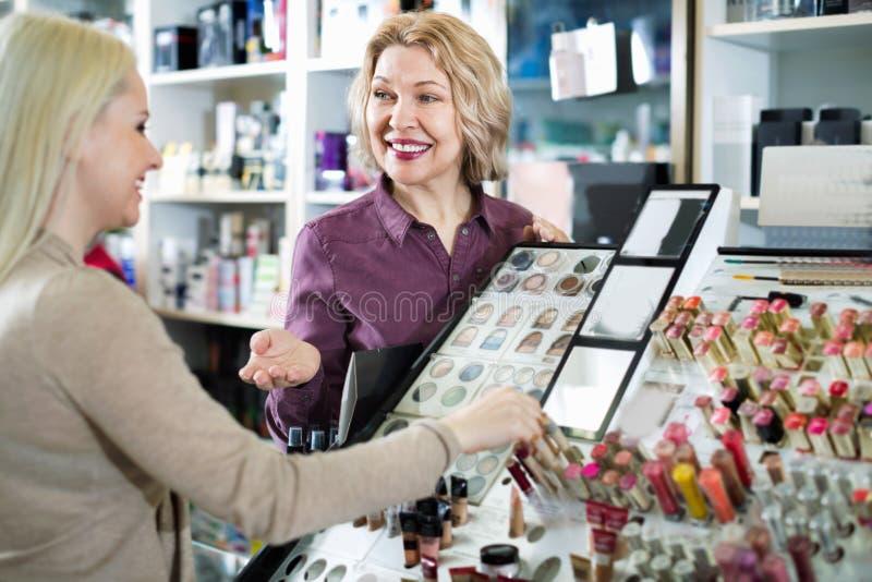 正面卖主帮助顾客在商店选择化妆用品 图库摄影