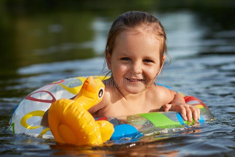 正面可爱的女孩游泳室外射击用特别设备,拿着她的橡胶玩具,恳切地微笑,有宜人 图库摄影