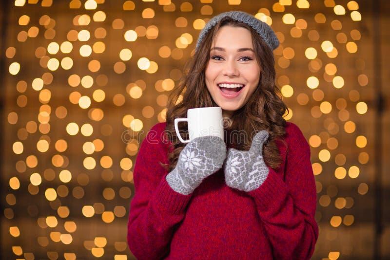 正面可笑的女孩饮用的咖啡和显示赞许 图库摄影