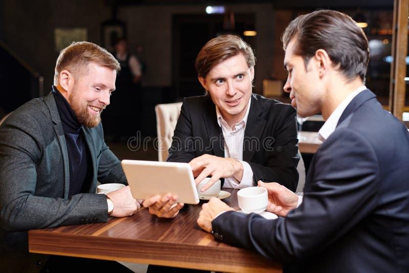 正面商务伙伴谈论项目在餐馆 图库摄影