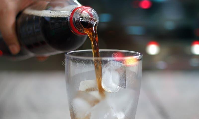 正面图、倾吐的可乐苏打饮料与冰和泡影 库存图片