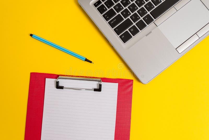 正面图开放时髦金属亭亭玉立的膝上型计算机色的剪贴板白纸板料标志色的背景 空的文本 图库摄影