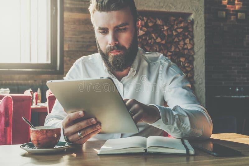 正面图 年轻有胡子的商人在咖啡馆坐在桌上,使用数字式片剂 在书桌上是笔记本,咖啡 库存图片