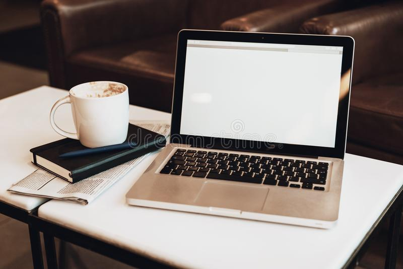 正面图 空的工作场所 在加奶咖啡桌是有黑屏的,咖啡膝上型计算机,笔记本,笔,报纸 免版税库存图片