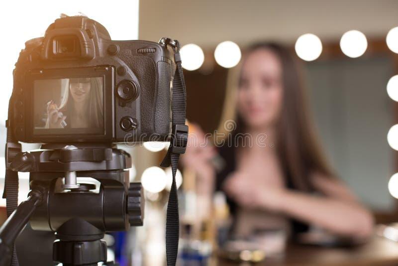 正面女孩摄制她的化妆vlog 免版税库存照片