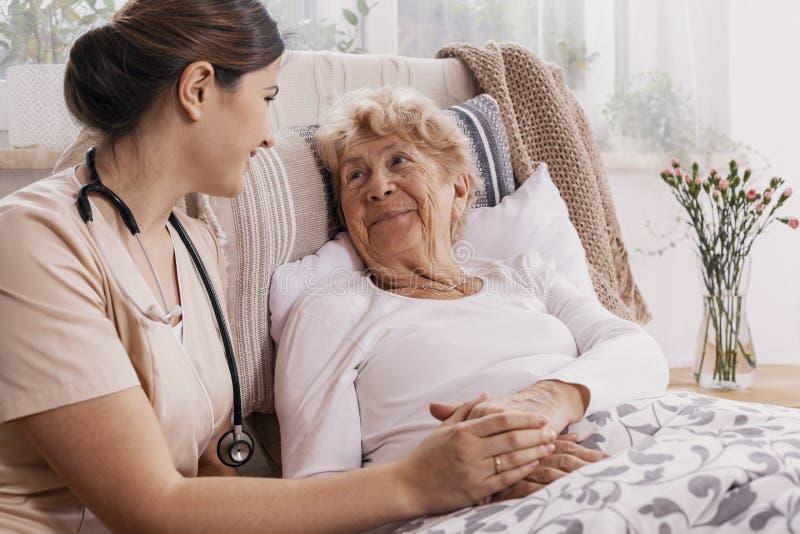 正面妇女在床上的,支持她的米黄制服的有用的医生 免版税库存照片