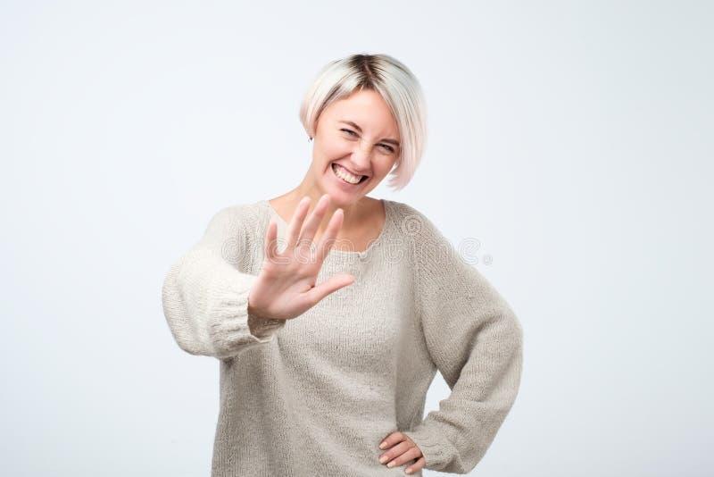 正面妇女在灰色毛线衣陈列中止姿态穿戴了,要求停止耍笑,她对笑疲乏 库存照片