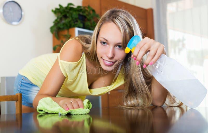 年轻正面妇女打扫灰尘桌 库存图片