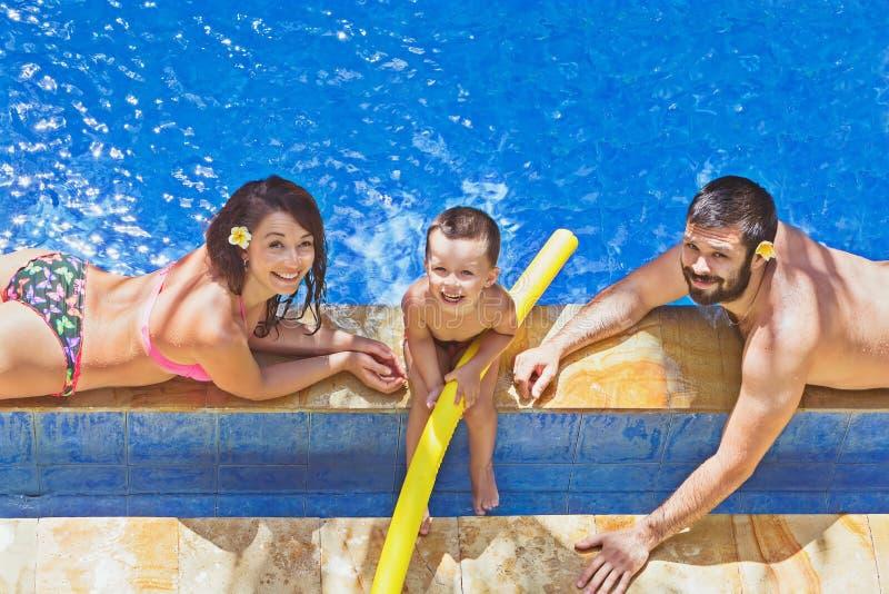 正面家庭在室外热带水池放松 免版税库存照片