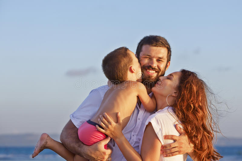 正面家庭画象在日落海滩的 图库摄影
