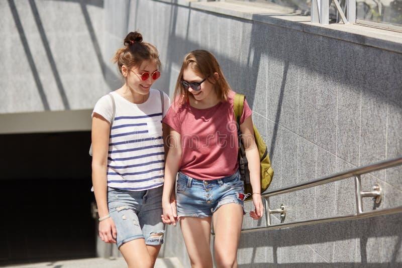 正面少女女同性恋者握手,运载背包,偶然T恤杉,并且短裤,在地下附近走一起有乐趣谈话 免版税图库摄影