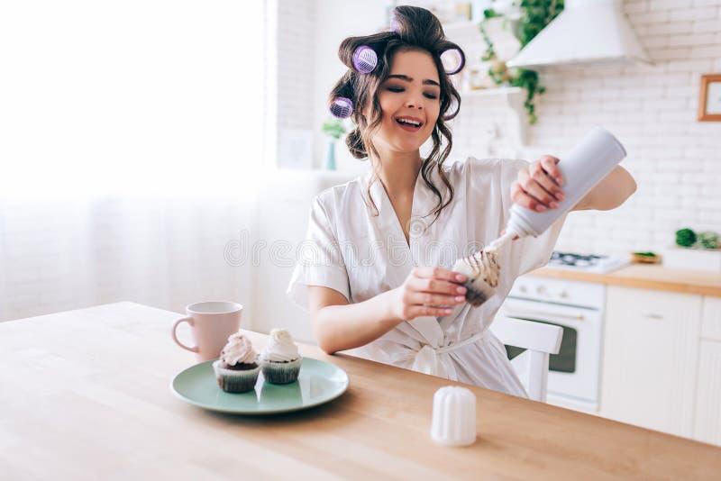 正面年轻女人在薄煎饼和微笑投入了白色奶油 女性管家坐在桌上在厨房里 享有生活 免版税库存图片