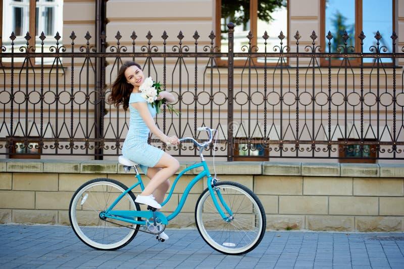 正面年轻女性有花的骑马蓝色自行车在她的手上下来铺了美丽的城市街道 库存照片