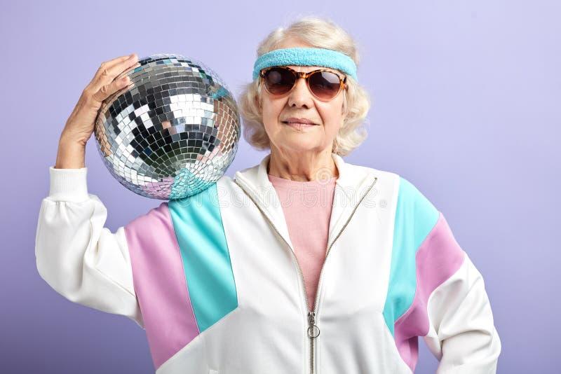 正面年长夫人拿着闪耀的迪斯科球,穿戴的微笑对照相机 图库摄影