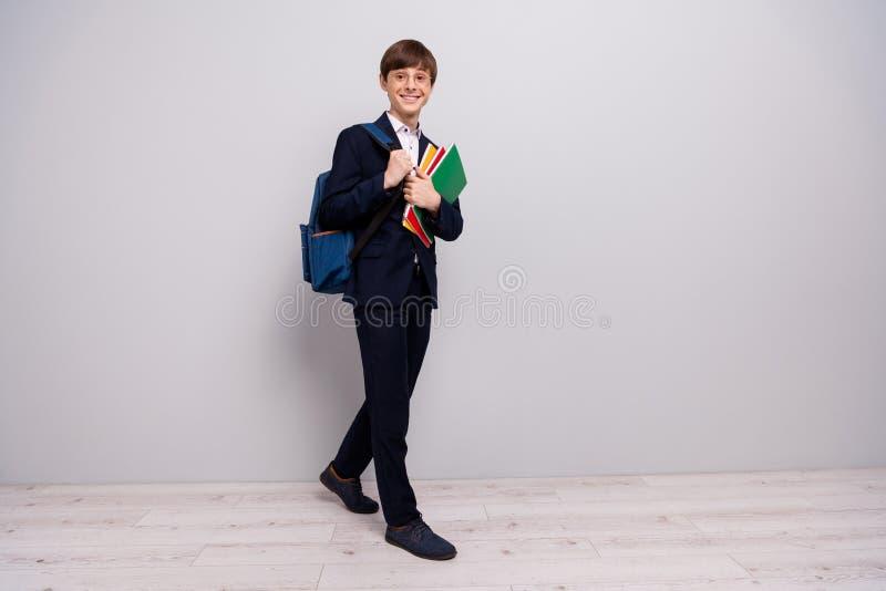 正面快乐的内容全长身体尺寸视图照片穿戴了时髦的夹克黑色燃烧物长裤衣服趋向 免版税图库摄影