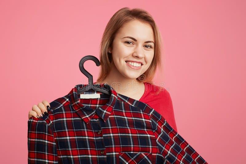 正面快乐的少妇给在挂衣架的时兴的方格的衬衣做广告,提议买它与低价,建议迪斯科 库存照片