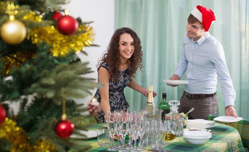正面愉快的人和女孩服务圣诞节桌 免版税图库摄影