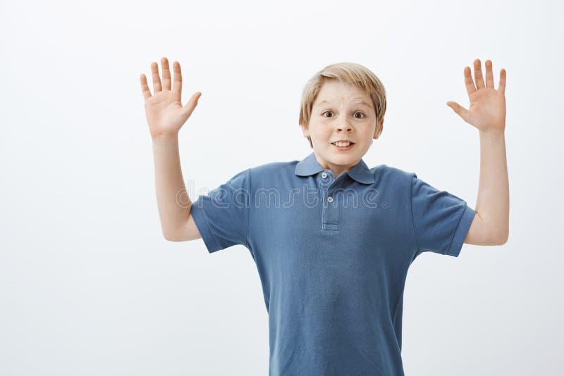 正面愉快的十几岁的男孩画象培养棕榈高在投降的蓝色T恤杉的惊奇和被捉住  免版税库存图片