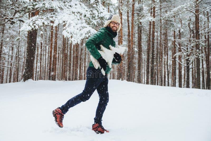正面愉快的男性室外画象获得乐趣,在冬天森林里走,享受美好的风景,并且新冷天,举行 免版税库存照片