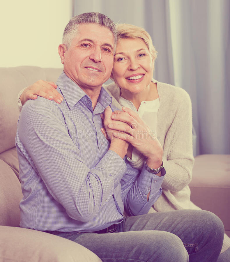正面成熟已婚夫妇在房子是温暖地被和解的af 库存图片