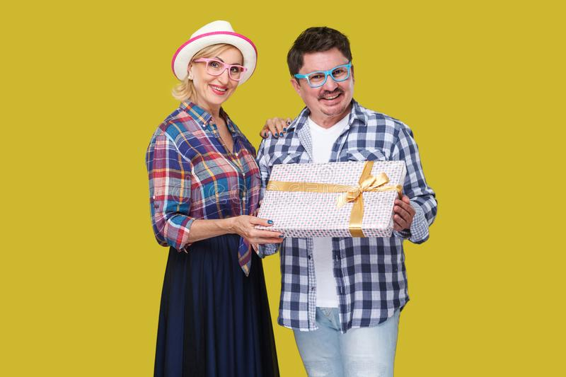 正面朋友、成人男人和妇女夫妇偶然方格的衬衣身分的在结合在一起使当前礼物盒旁边, 库存图片