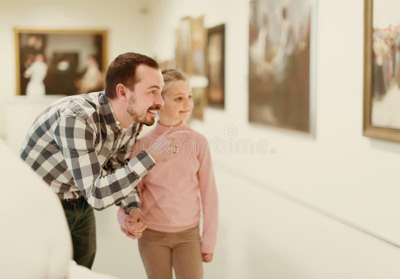 正面父亲和女儿关于绘画在博物馆 免版税图库摄影