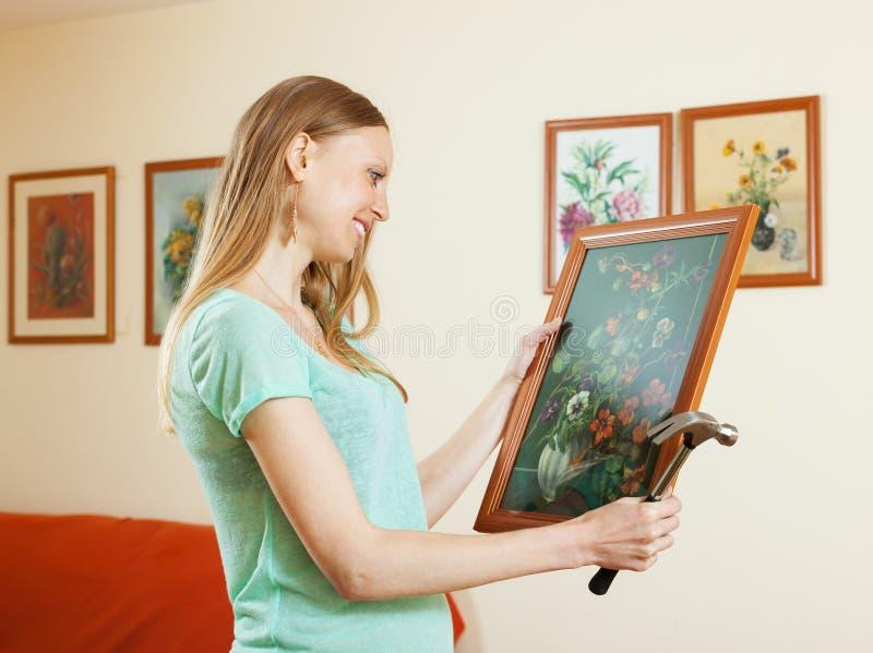 正面白肤金发的女孩垂悬的图片 免版税库存照片