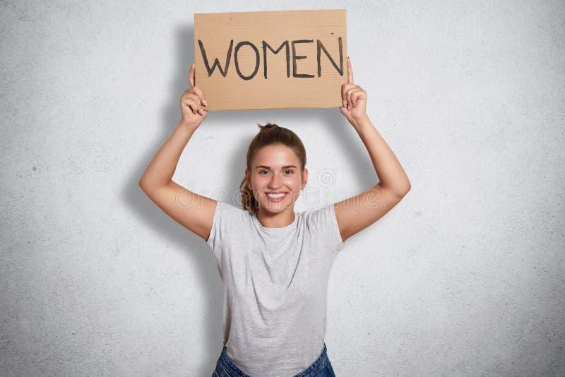 正面精力充沛的女权举行的标志室内射击与题字妇女的在她的头上,举她的胳膊,支持 库存照片