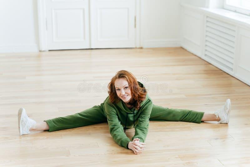 正面红发妇女水平的射击做pilates锻炼,drssed在绿色田径服,有好的灵活性,实践 图库摄影