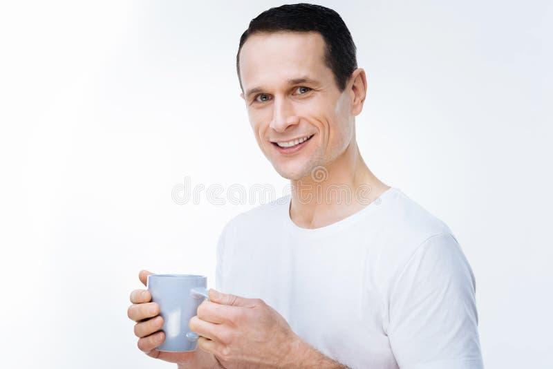 正面英俊的人饮用的茶 免版税库存图片
