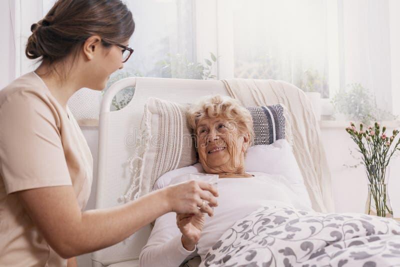 正面资深妇女在床上的,支持她的米黄制服的有用的医生 库存图片