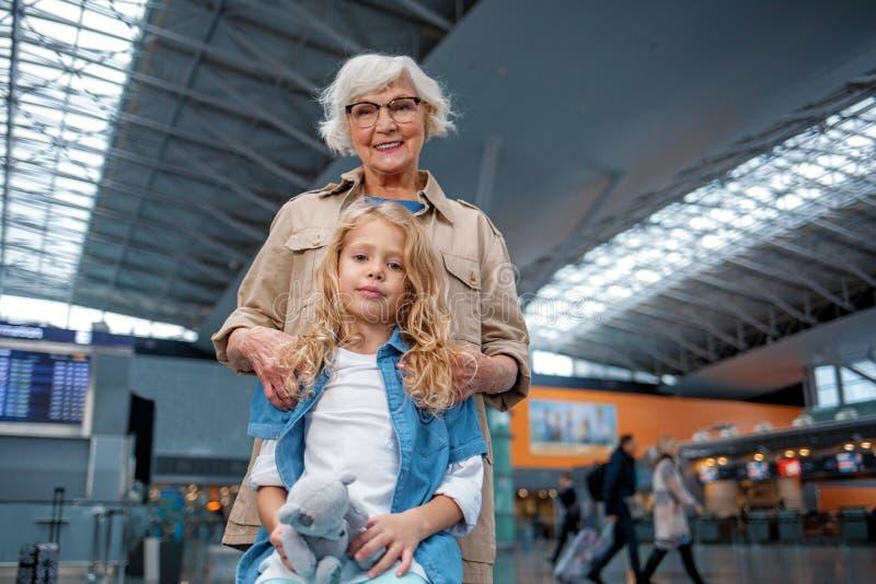 正面资深祖母在机场大厅拥抱她的孙女 库存图片