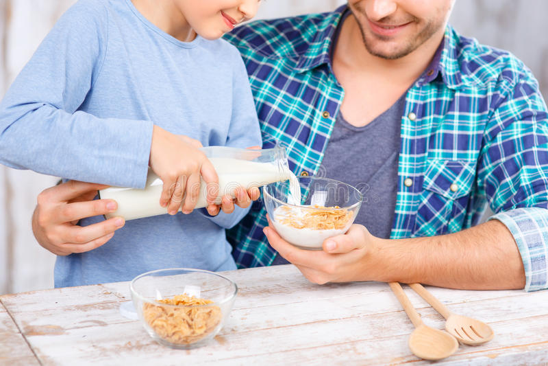 正面食用父亲和的女儿早餐 免版税库存图片