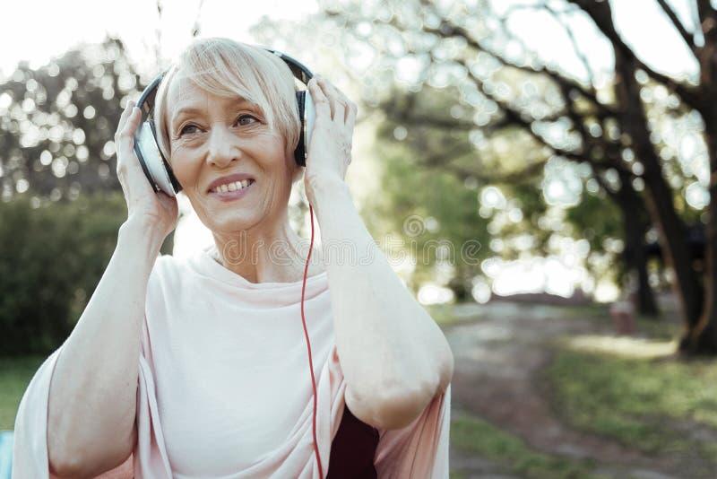 正面高兴女性听的音乐 免版税库存照片