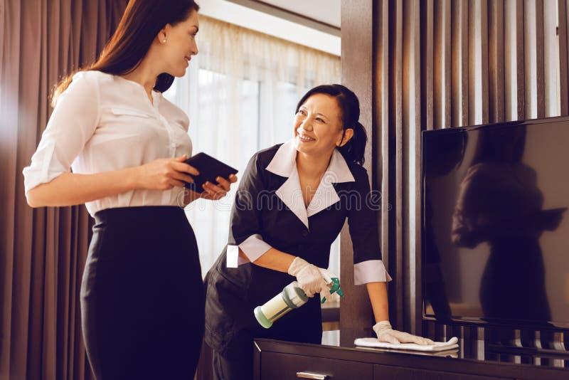 正面高兴女服务生擦亮的家具 免版税库存图片