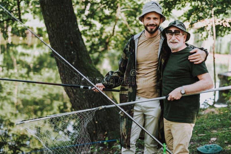 正面高兴拥抱他的父亲,当钓鱼时 免版税库存图片