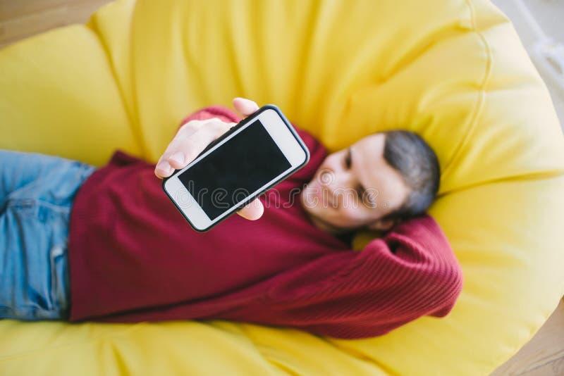 正面年轻人行家送电话照相机,当坐在一个黄色椅子袋子时 在电话的重点 免版税图库摄影