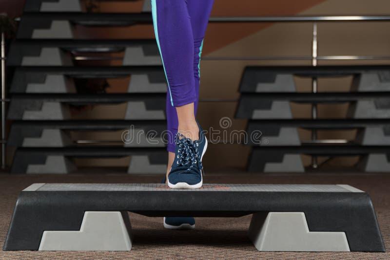 步平台 在步平台的脚 在健身房的类 健身有氧运动 库存照片