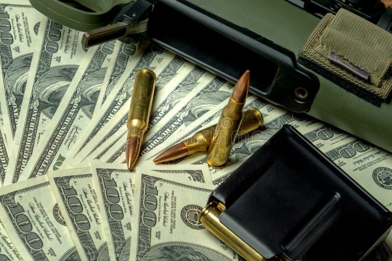 步枪、杂志和弹药筒在一百元钞票 罪行的,杀手,受雇用的刺客,恐怖主义概念 图库摄影