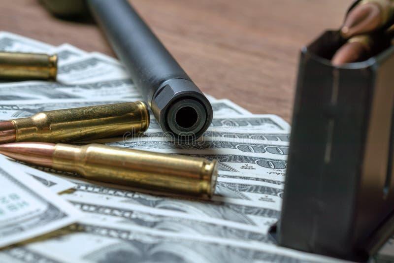 步枪桶、杂志和弹药筒在金钱 罪行的,杀手,受雇用的刺客,恐怖主义,战争概念 免版税库存图片