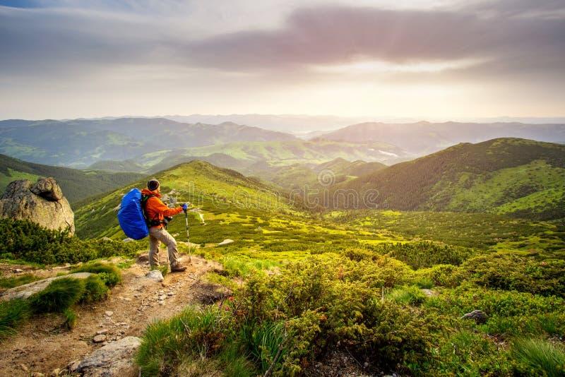 步行与背包的旅客人敬佩一个美好的风景 HDR foto 免版税库存照片