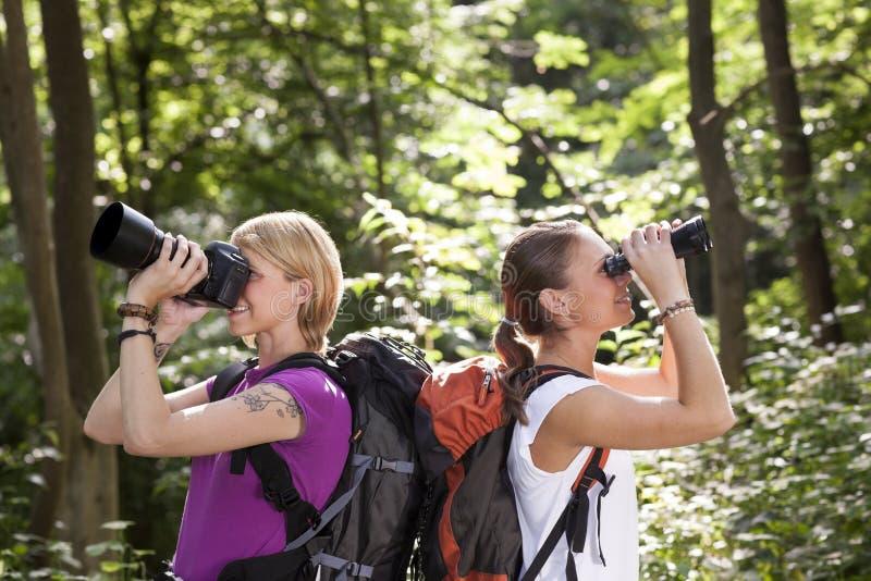 步行和查找与双筒望远镜的二名妇女 免版税库存图片