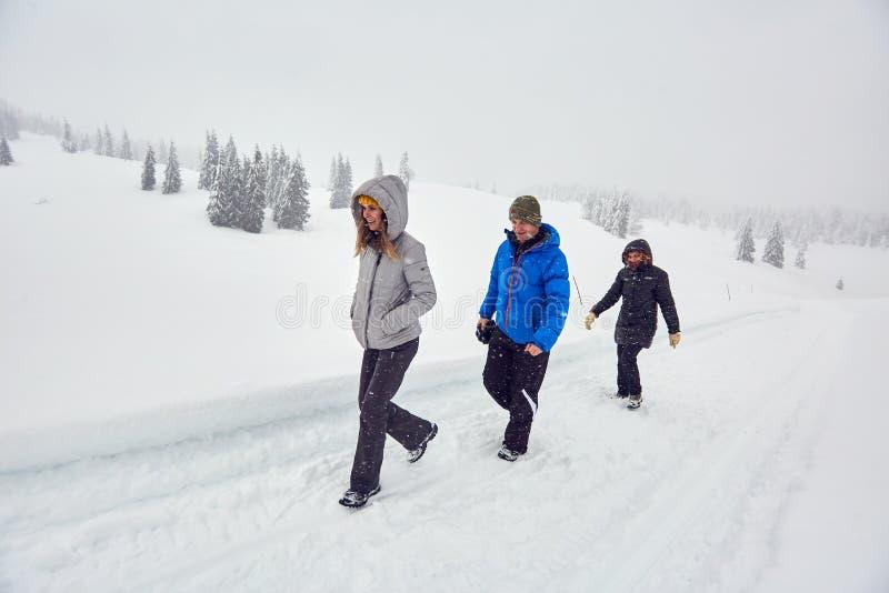 步行在一串多雪的足迹的朋友 免版税图库摄影